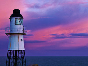A lighthouse against a beautiful sunset on the Isles of Scilly.